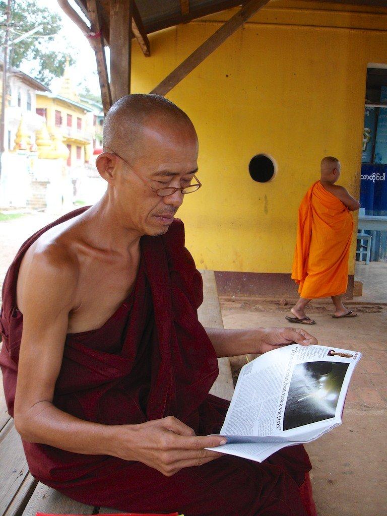 Burma, Mt Popa, monk reading news magazine