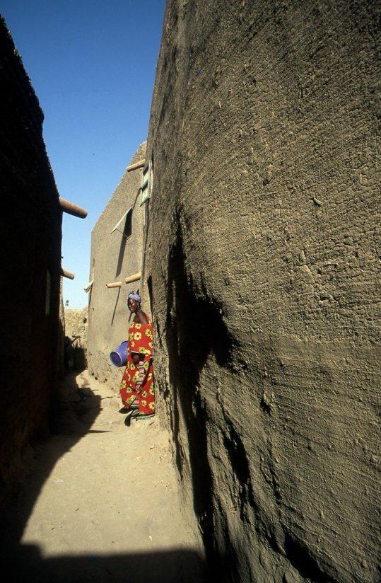 Mali, Djenné backstreet, woman and mud walls