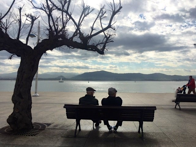 Old men on a bench silhouetted against the bay of Santander